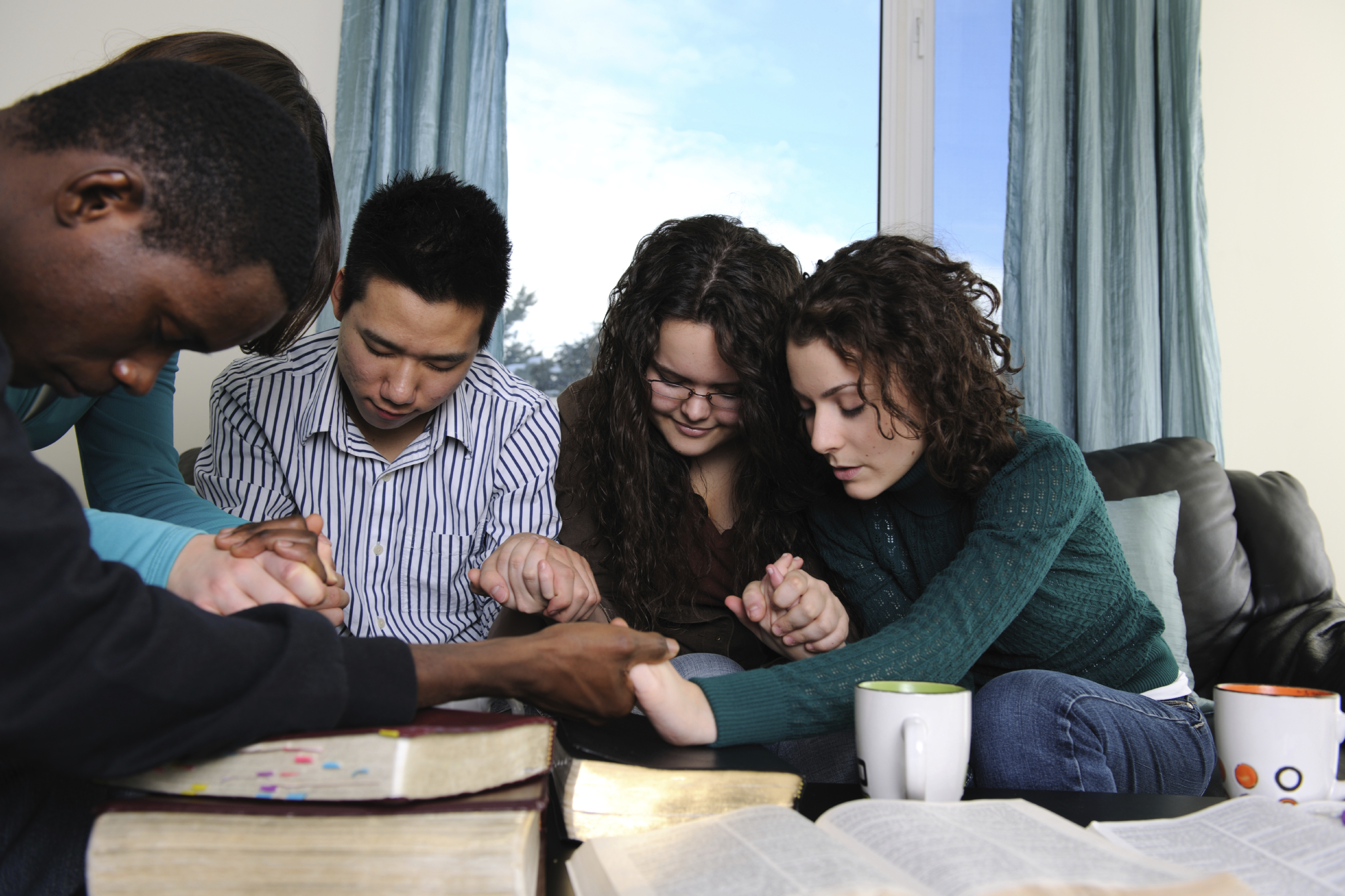 Five diverse college students praying together while holding hands.